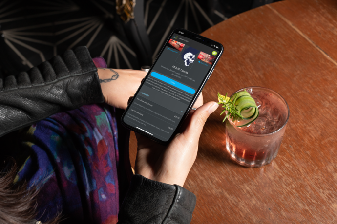 Customer scanning a QR code on a drinks ordering app in a bar