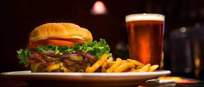 A burger and a pint of beer on a pub table